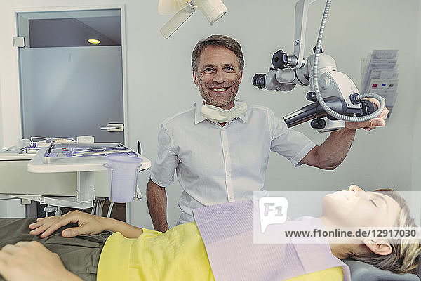 Dentist examining his patient  using dental microscope