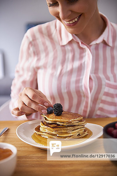 Young woman garnishing fresh pancakes with berries