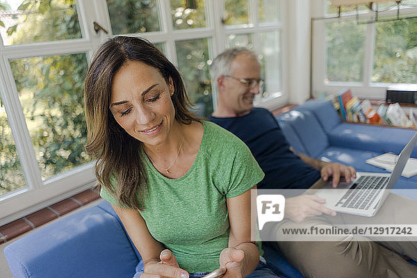 Mature couple sitting on couch at home with woman using cell phone and man using laptop