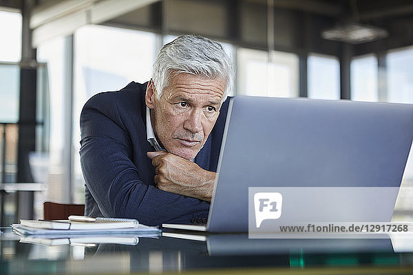 Businessman sitting at desk  trying to solve a problem