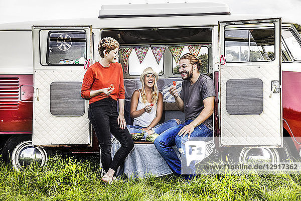 Happy friends having picnic in a van parked on field