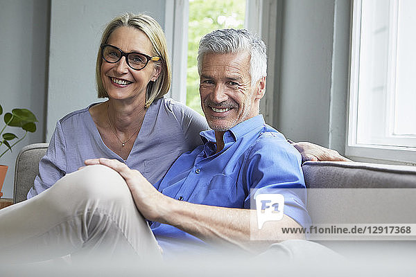 Portrait of smiling mature couple on couch at home