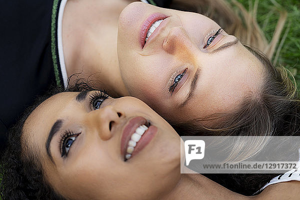 Two girlfriends relaxing in a park  lying on grass