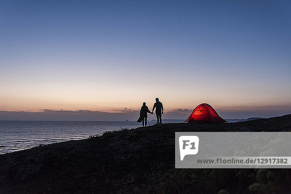 Romantic couple camping on the beach  walking in twilight  holding hands