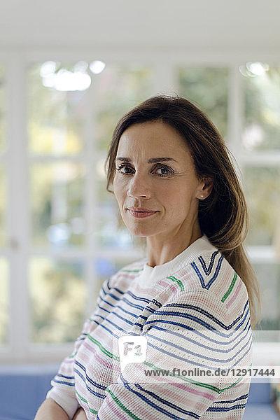 Portrait of confident mature woman at home