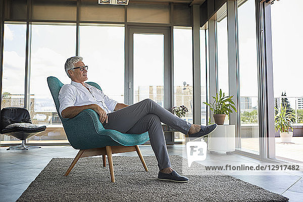 Mature man relaxing in armchair at the window at home