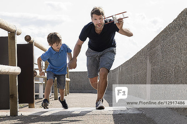Father and son running with toy plane