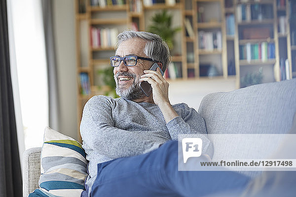 Mature man on the phone sitting on couch at home looking out of window