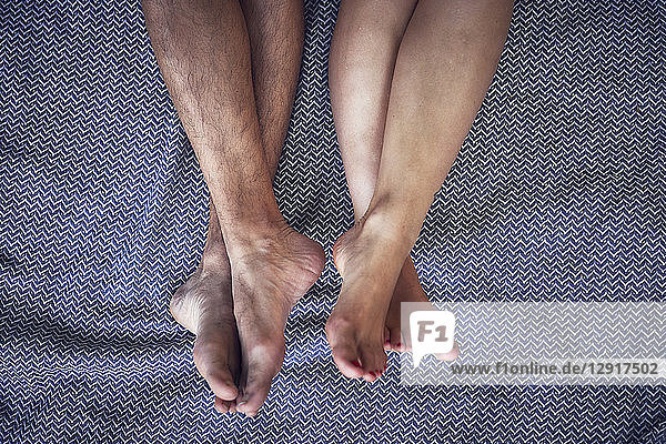 Barefoot legs of young couple  lying on a blanket