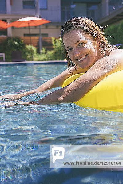 A smiling young woman floats on a yellow inflatable in a pool in summer.