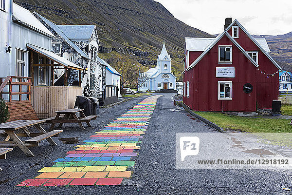 Rainbow colored brick road between houses leading to small church at edge of town  Seydisfjordur  Iceland