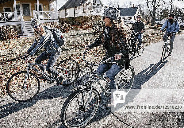 Group of friends biking through sunny village in autumn  Portland  Maine  USA