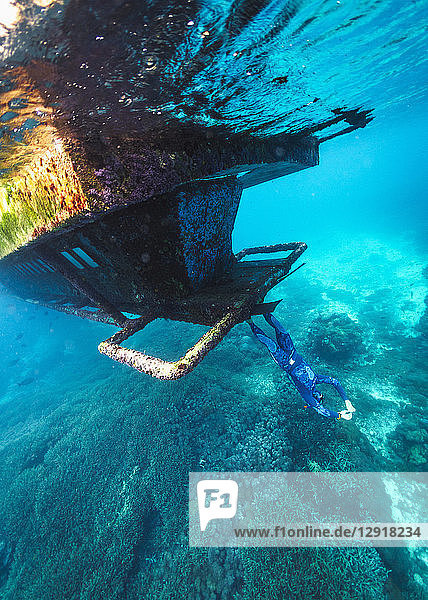 Underwater view of diver standing upside down on sunken shipwreck  Nusa Penida  Bali  Indonesia