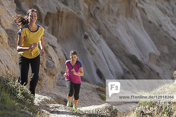 Two women running in sandstone area near Torrey Pines State Park in La Jolla  San Diego  California  USA