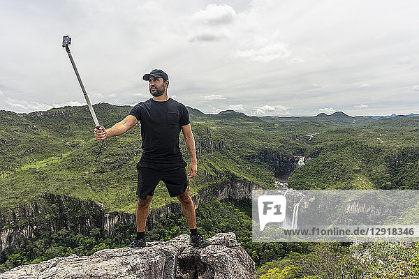 Man taking selfie with selfie stick in cerrado landscape  Chapada dos Veadeiros  Goias  Brazil