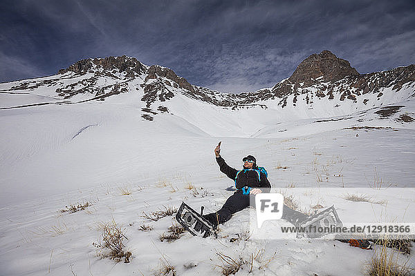 Mountaineer taking selfie while lying on snow below Donaldson Peak in the Lost River Mountain Range  Idaho  USA