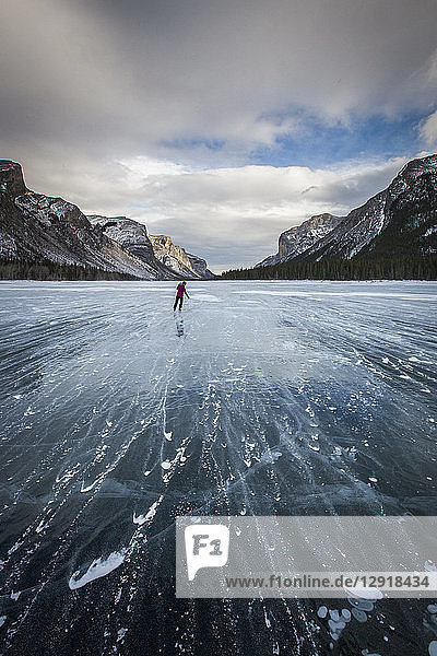 Distant rear view shot of person ice skating on frozen Lake Minnewanka in winter  Banff National Park  Alberta  Canada