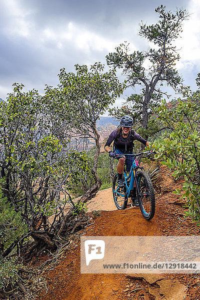 Female mountain biker riding along dirt trail  Sedona  Arizona  USA