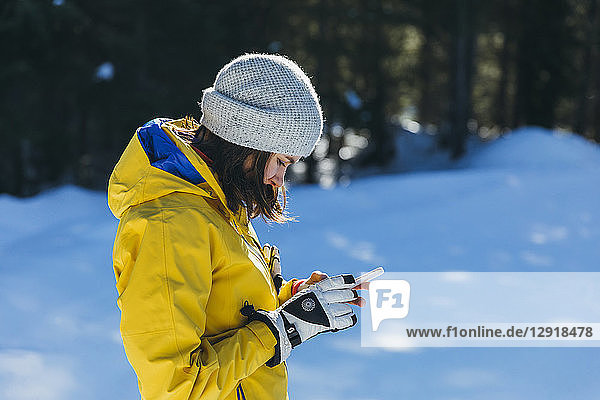 Side view shot of young woman using phone outdoors in winter  Whistler  British Columbia  Canada