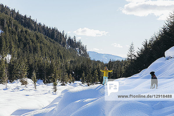 Distant view of woman playing with dog in natural setting in winter  Whistler  British Columbia  Canada