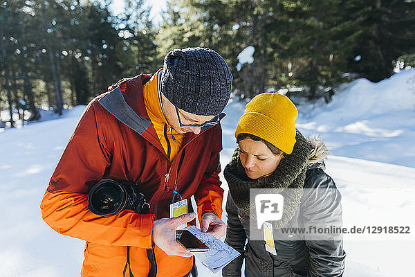 Waist up shot of man and woman checking map while hiking in winter  Whistler  British Columbia  Canada