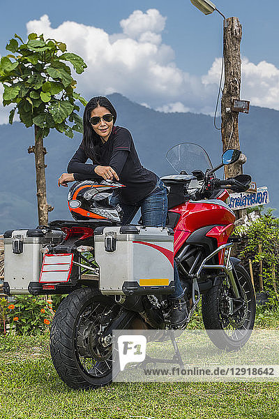 Portrait of woman posing on top of motorcycle with hill in background  Nan ¬ÝMueang¬ÝChiang¬ÝRai¬ÝDistrict  Thailand