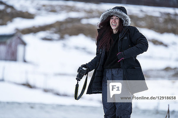 Three quarter length shot of laughing woman with camera in winter Tromso  Troms County  Norway