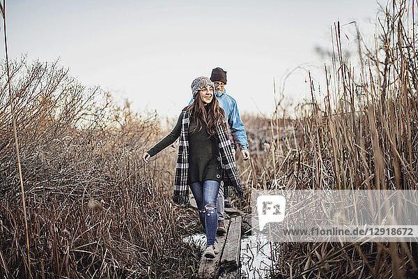 Couple walking on log bridge over marsh  Peaks Island  Maine  USA
