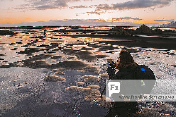 Female photographer crouching while taking picture at sunset  Iceland