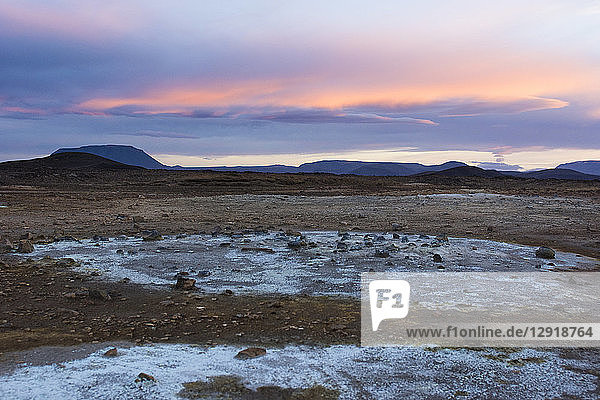 Blue coloured minerals  left behind by volcanic mud puddles and fumes  contrast with the orange coloured sky in Hverarˆšˆ'ndor Hverir Geothermal Area at Namaskard Pass  North Iceland.