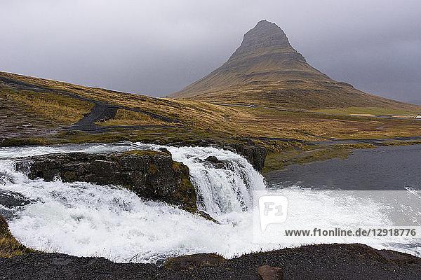 Scenic view of splashing Kirkjufellsfoss waterfall and Kirkjufell mountain on gray day  Iceland