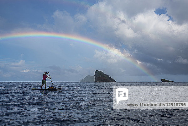 Side view of man paddleboarding in sea under rainbow  Misool  Raja Ampat  Indonesia