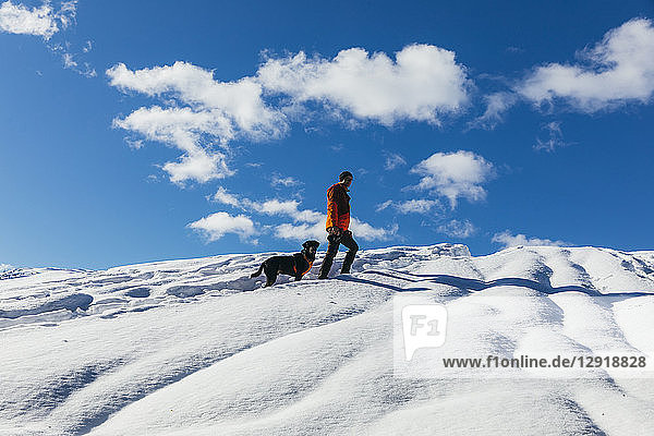 Clouds over man¬Ýsnowshoeing with pet dog on¬Ýsnowcapped¬Ýhill  Whistler  British Columbia  Canada
