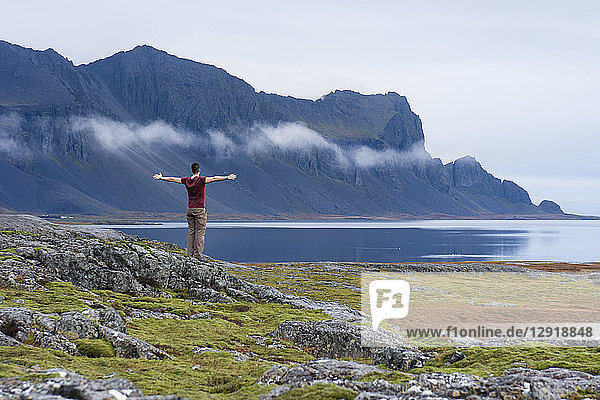 A young man wearing a purple t-shirt stands on top of a moss covered rock as he opens his arms and admires the mountainous coastline of East Iceland  Hringvegur  East Iceland  Iceland