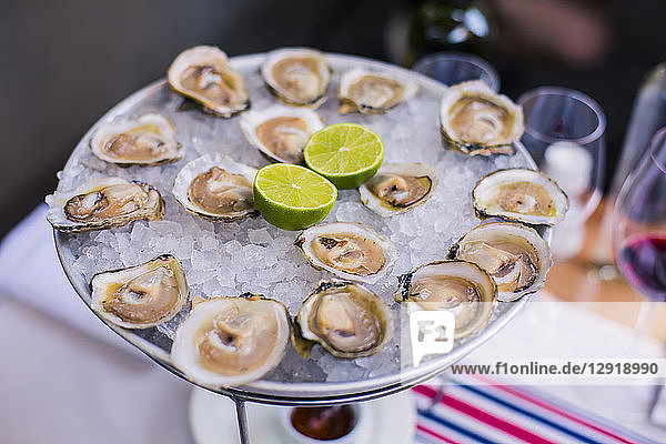 Fresh oysters with ice and limes on stand