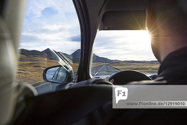 An over the shoulder viw of a young man driving the Ring Road as the sun begins to set  in North Iceland.
