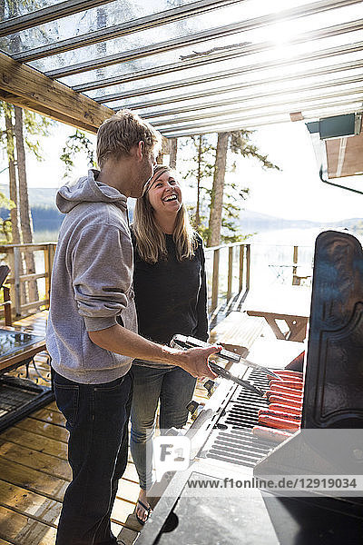 Side view of man cooking sausages on barbecue grill and smiling woman