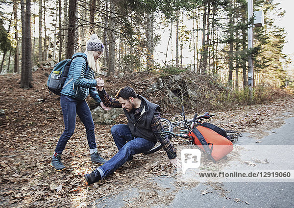 Young woman helping up man who has just crashed his bike while riding through woods  Portland  Maine  USA