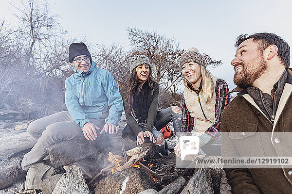 Four adult friends warming up around campfire while camping on rocky coastal beach in autumn  Portland  Maine  USA