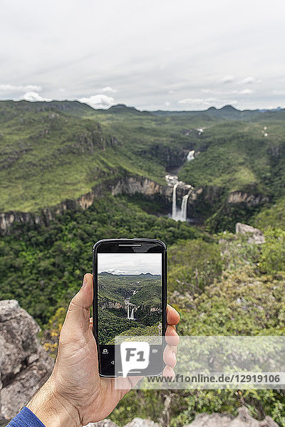 Hand holding mobile phone taking a picture of beautiful cerrado natural landscape with waterfalls in Mirante da Janela  Chapada dos Veadeiros  Goias  central Brazil