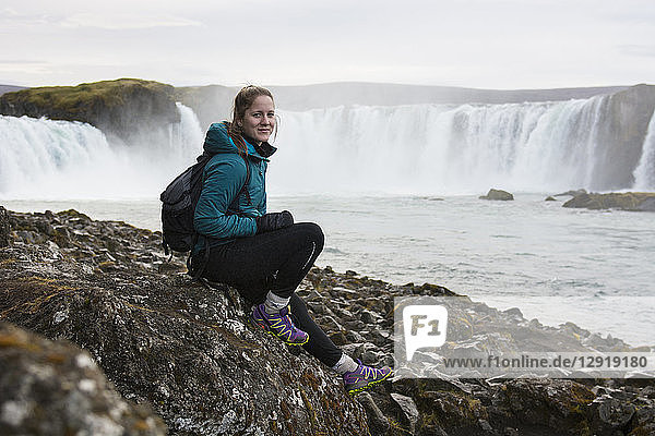 Portrait of female hiker sitting against splashing Godafoss waterfall and smiling at camera  Iceland