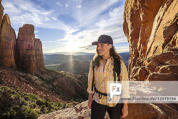 Portrait of female hiker standing and smiling at Cathedral Rock with setting sun in background  Arizona  USA