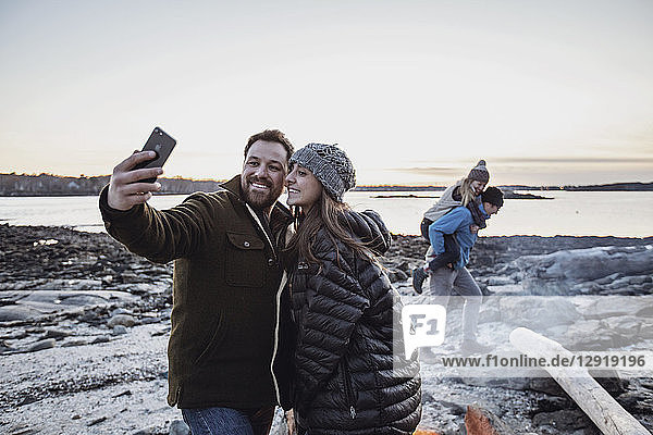 Adult couple taking selfie in front of campfire with friends piggybacking in background  Portland  Maine  USA