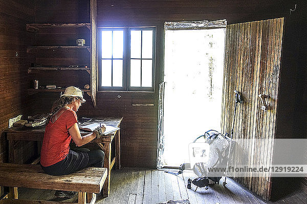 A thru hiker takes a break at Theodore Roosevelts Cabin on the Muav Saddle  far out on the North Rim of the Grand Canyon  and signs a storied trail register  Arizona  USA