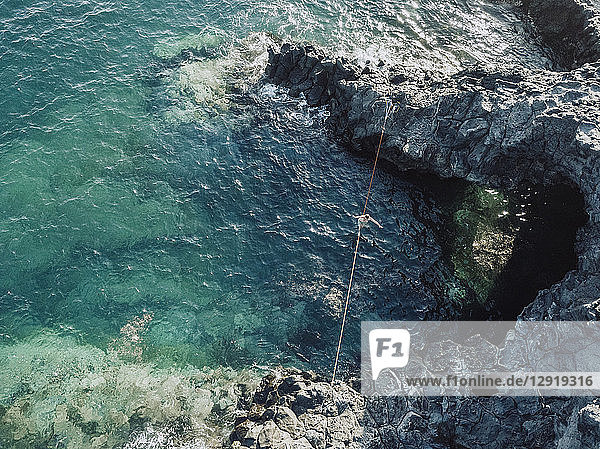 Aerial view of young shirtless man balancing across tightrope over coastal water ¬ÝTenerife  Canary Islands  Spain