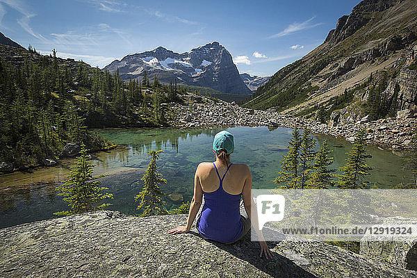 Rear view shot of female hiker sitting on shore of Lake O'Hara  Yoho National Park  Alberta  Canada