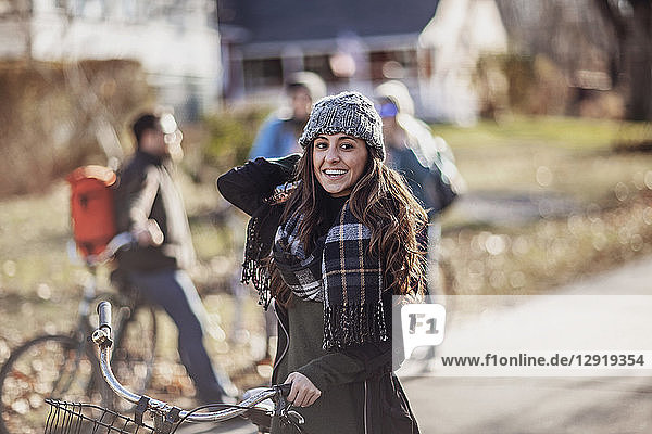 Portrait of young woman wearing scarf and knit hat standing with bicycle and smiling at camera  Portland  Maine  USA
