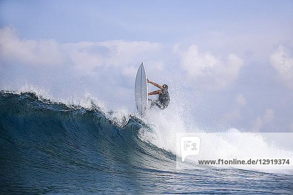 Male surfer riding wave against clouds  Male  Maldives