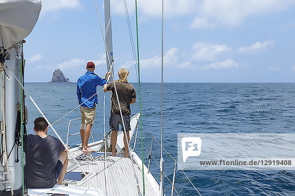 Rear view of group of three men on sailboat sailing in sea