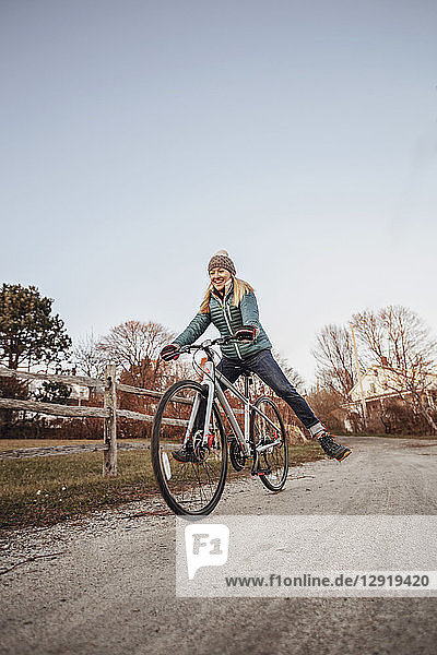 Young woman riding bicycle along countryside dirt road beside wooden fence  Portland  Maine  USA